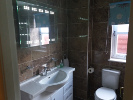 The main bathroom with an LED lit mirror and a heated towel rail.